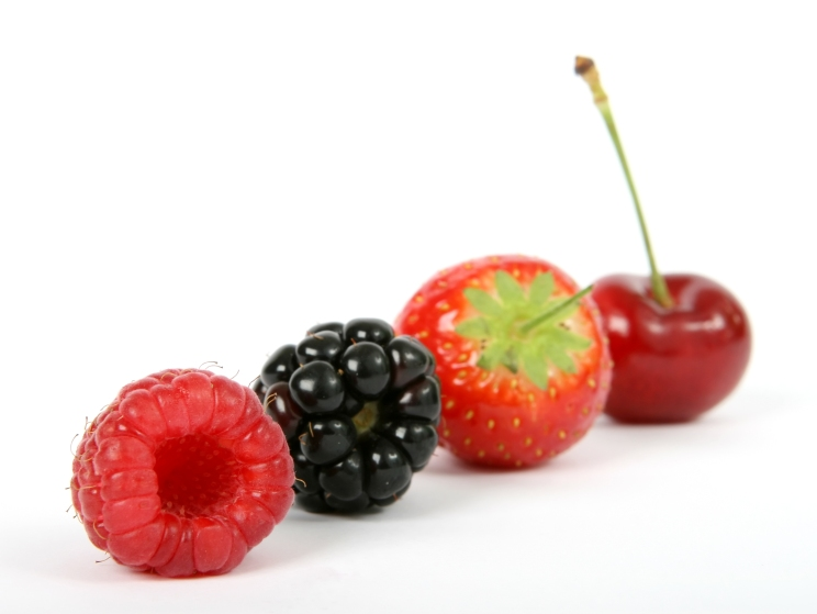 Summer fruit salad ingredients, strawberry, raspberry, cherry and blackberry, macro close up on white with copy space